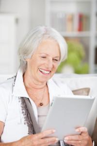 Ältere Dame mit Tablett und Skype